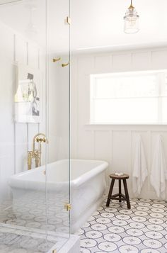 White bathroom with patterned tiled floor and gold accents