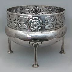 This is not contemporary - image from a gallery of vintage and/or antique objects. A. E. JONES (1879-1954)  An Arts & Crafts, hammered silver fruit bowl with a rose frieze border.  The bowl supported on four legs.