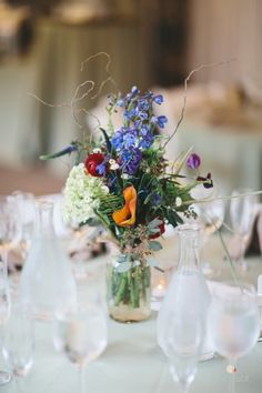 Crystal-clear bottles filled with fresh-cut blossoms and organic wisps for the centerpieces at Adrienne and Josh's Tyler wedding - by Buttercup: Readyluck Photography.