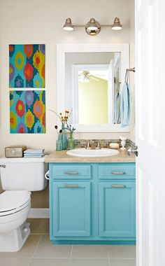 Contemporary Style: Small Bathroom Update with a Pop of Color -- This small bath is simple but snazzy on a budget! Bright blue paint makes the vanity look like new. A 3-light fixture illuminates the brushed-nickel faucet and towel ring, while the tiled back-splash, moulding-framed mirror, and laminate countertop create definition. Colorful DIY wall art brings all the colors together.