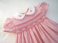 What baby girl doesnt look just precious in an adorable soft baby pink floral hand smocked dress?! Well, this one is sure to be the favorite. The fabric is a cotton print design that is irresistible and the smocking is just beyond gorgeous in its coordinating colors of white and soft to dark pink. Embroidered roses are scattered across the front. And the peter pan collars edged with matching piping also each feature a little rose detail. In its entirety this little dress is made with utmost…