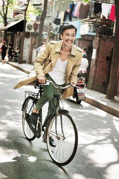トレンチコートを着て自転車に乗る男たち。