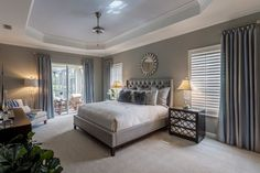 This master bedroom features a grey color scheme with accents including mirrored bedside tables, glass lamps, and a round mirror hung above the bed.