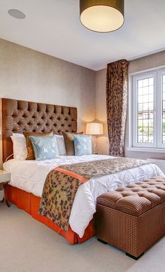 Truly unique and elegant bronze colored bed with headboard matching colored bedding and ottoman bench in a contemporary home in Glasgow!