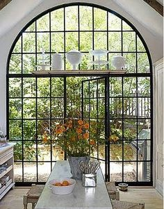 Window/door wall with black steel frames. Love the shelf holding white containers and cake stands.