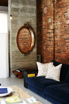 Love the way copper mirror (incredible piece BTW) brings warmth of brick onto cement support. And the blue from the sofa is sublime w/brick!  Via: Pinecone Camp: City Living in Gastown / designer: Omer Arbel