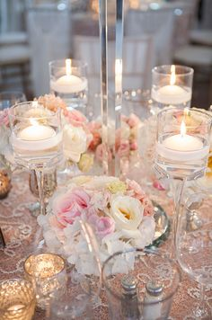White floating candles are placed in tall glass stands and matched by metallic vases holding pink and white flowers.