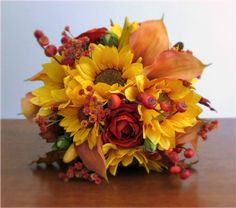 Custom silk and real touch flower bridal bouquet in shades of yellow, orange, red, and brown, featuring sunflowers, calla lilies, ranunculus, gypsophila / baby's breath, rose hips, pine cones, wheat, lily buds, and fall leaves, and wrapped with burlap and lace. #fallwedding #autumn #PosiesPearls