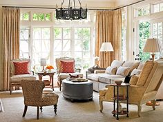 Traditional elements fit into a casual setting in this family room, where light pours in through large windows dressed in an antique-looking Rose Tarlow fabric. - Traditional Home®    Photo: Emily Followill