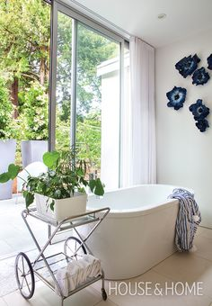 To create the feel of alfresco bathing in her own principal ensuite, designer Bobbie Burgers opted for a sliding door over windows, and brought some greenery indoors. | Photographer: Kim Christie
