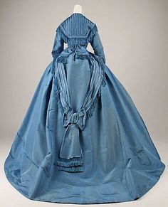 Rich blue gown (circa 1867) Classic elements of gowns from this era - high neckline, sloping shoulders with drop sleeve.  Fitted bodice with cinched waist swells to full bell skirt.  This dress has a slight train with an interesting treatment on the back of the skirt: a low, fringe-trimmed swag with a large bow (with fringed sashes) positioned about knee height.