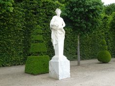 Topiaries and classical statue, at the Palace of Versailles, France