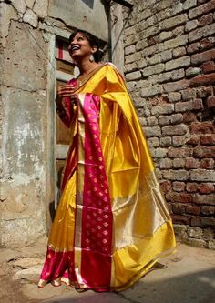 Yellow banarasi silk saree with pink border by Resha