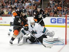San Jose Sharks goaltender Alex Stalock eyes the puck with is pad down to prevent a goal by Patrick Maroon of the Anaheim Ducks (Oct. 3, 2015).