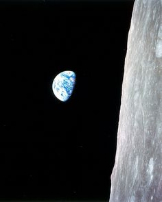 This view of the rising Earth greeted the Apollo 8 astronauts as they came from behind the Moon after the lunar orbit insertion burn. The photo is displayed here in its original orientation, though it is more commonly viewed with the lunar surface at the bottom of the photo. Earth is about five degrees left of the horizon in the photo.