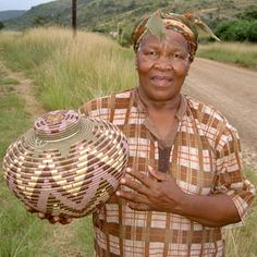 Renowned Zulu masterweaver Laurentia Dlamini, holding one of her baskets. | Laurentia is the only living weaver from the original resurgence of basket weaving that happened in South Africa in the 1950's. She was one of the original 4 weavers that started a weaving co-op in 1972 | She is 75 years old now and has been weaving for more than 60 years.