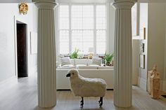Photography by John Spinks  Romualdez added the columns framing the window and the Lalanne sheep. Lynda Benglis's gilded plaster sculpture is above the door to the library at lef
