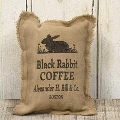 """Black Rabbit Coffee Pillow is a soft burlap cotton pillow with a primitive, fringed edge detail. Pillow displays a vintage-style advertisement for, """"Black Rabbit Coffee."""" Measures high by wide. Made in the USA!"""