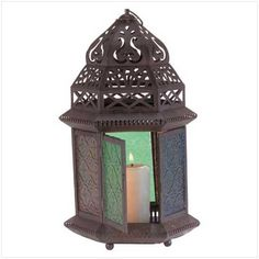 """33144 The graceful cutouts in this candle lantern's shell throw dancing laceworks of light, while patterned multi-colored glass panels cast a halo of color. Suitable for hanging, or use as a free-standing lamp. Uses pillar or votive candles (not included). Metal with colored glass panels. 6 1/2"""" x 7 1/2"""" x 13"""" high."""