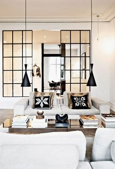 Black  white living room with iron framed doors, black pendant lights and white sofas.