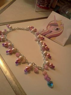 """A princess Cadence inspired necklace, made with an 18"""" silver plated curb chain with heart-shaped toggle clasp closure. Glass beads, glass pearls and acrylic pearls. A blue rhinestone heart (just like her cutiemark!) dangles below three stones in the center of the necklace. Perfect for cosplay or..."""