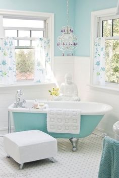 Blue and white bathroom decor style - love the chandelier above the claw foot bath tub