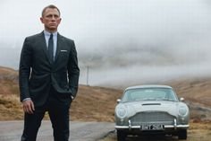 Daniel Craig standing next to an Aston Martin DB5