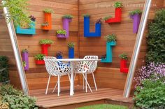 Herbs in hanging container pots in modern bold colors on deck with chairs and table furniture and plantings #garden