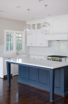 White and blue kitchen boasts a pair of clear glass pendants illuminating a blue center island with tapered legs topped with white quartz.