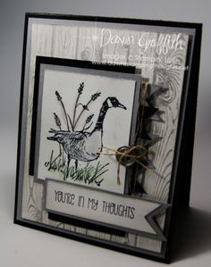 "By Dawn Griffith. Background: Black card base then gray mat then popped up white mat stamped with ""Hardwood"" (Stampin' Up). Foreground: Goose from ""Wetlands"" (Stampin' Up) stamped on white rectangle layered on gray mat then offset black mat. Black and gray banners tucked under piece. Button and twine added on top. This piece popped up on card. Sentiment stamped on white banner and layered on gray banner; popped up on card."
