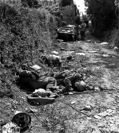 West of Sainteny, France. American soldiers inspect a destroyed German convoy. In the foreground, the bodies of three German parachutists of the FJR.6 (Fallschirmjäger) lie dead. In the background a Schwimmwagen VW 166, at side two GI'S of the 4th US Inf Div including one wearing an arm-band of the Red Cross. 16 july 1944
