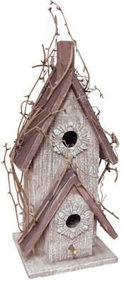 The Country Double-Roof Birdhouse is made from rough, white-washed wood for a weathered appearance. Grapevine accents and decorative molding around the holes add to its primitive charm. The roof is co