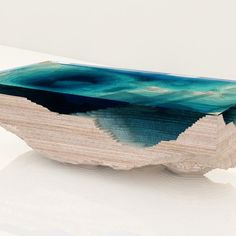 with multiple layers of stacked glass and wooden slices, duffy london has built 'the abyss table', replicating the dramatic depths of an indigo ocean. the design creates a geological cross-section of the sea, completing the table as a 3-dimensional model of a geological map. 'I was looking into sheets of thick glass at my glass manufacturer's factory, and noticed how the material darkened a..