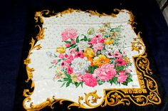 This listing is for a beautiful Vintage Designer Floral Silk Scarf measuring 34 x 34. This silk scarf features an absolutely gorgeous floral bouquet at its center. There is a diamond woven jacquard type design throughout the scarf. It features a black border with gold filigree