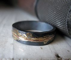 This design is simple and understated, yet rustic and OOAK. The ring is sterling silver, hammered for texture. A river of 14K rose gold extends around the ring in the center of the band, and is accented with 14K yellow gold. Finally, the ring is oxidized to a dark gray, then