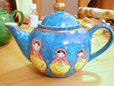 Russian Dolls teapot decorated with matryoshka nesting doll images on background of blue winter sky, gold highlights on rim and knob, ceramic