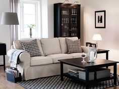 """Ein Wohnzimmer mit EKTORP 3er-Sofa mit Bezug """"Tygelsjö"""" in Beige, HEMNES Beistelltisch, HEMNES Couchtisch und HEMNES Vitrinenschrank in Schwarzbraun"""