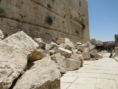 Looking south down the Herodian street along the Western Wall at the southwest end of the Temple Mount.  Robinson's Arch. Stones from the Jewish Temple and broken Herodian ashlars lay at the base of the Temple Mount wall right were they landed in 70 AD when the Tenth Roman Legion destroyed the temple and its courts.