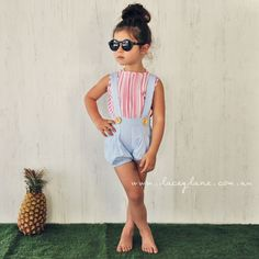 Bronte Blouse for $39.95:  -Polycotton  -Button up back with wooden buttons  -Pink & white striped fabric  -Detailed pleated front  -Regular fit    Model is wearing size 3 and paired with Lotti Suspender Bloomers and Chester Pucker Bloomers with matching Chester Suspenders and Matte Black Sunglasses.
