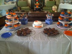 Dessert table for Florida Gator baby shower- marshmallow pops, football brownies, gingham cupcake liners in florida colors and custom cupcake holders