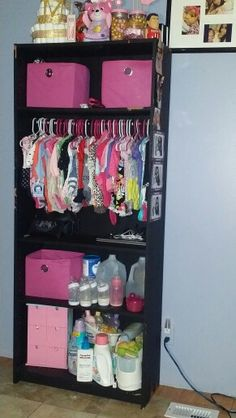 Brown bookshelf converted into black baby closet.
