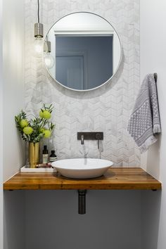A modern powder room with marble look chevron tiles and concrete look floors. Round mirror, floating timber vanity and gunmetal tap wear. Built by R.E.P Building. Photography by Hcreations.