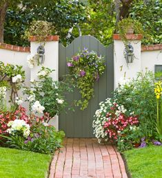 Pretty flowering plants frame this garden gate, creating a lovely doorway from…