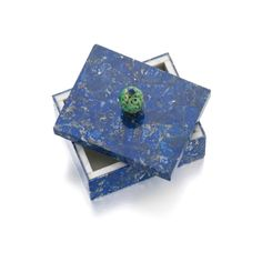 LAPIS LAZULI AND JADE BOX, CARTIER, CIRCA 1945 The rectangular box covered in mosaic lapis lazuli, topped by a removable lid capped with a carved jade rondelle surmounted by a piece of facetted lapis, measuring approximately 110 x 86 x 70mm, indistinct French assay mark, fitted and numbered case by Cartier, gross weight approximately 750 grams. Estimate 8,174 - 14,169USD LOT SOLD. 13,624 USD