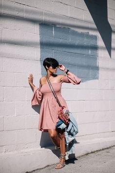 mauve off shoulder dress + jean jacket + colorful purse + black and white printed sandals