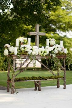 Gorgeous alter table with hydrangea, ivy, moss and a cross.                                                                                                                                                                                 More