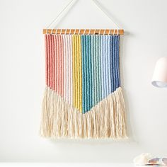 Brighten up a kids room, nursery or playroom with the colorful hues on our Vertical Rainbow Wall Hanging. With a variety of vertical stripes in a rainbow of colors, this unique piece of kids decor is made by hand.