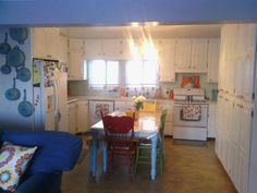 Kitchen. Painted cabinets white. Orange & teal decor & Alice in wonderland style table & chairs. Cute & eclectic.