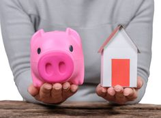 woman holding piggy bank and model home