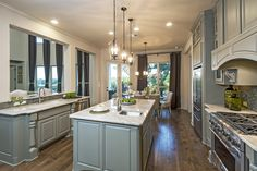 Imagine cooking dinner in this beautiful kitchen with green cabinetry, spacious granite countertops, and charming wood floors. #dreamhome #kitchen